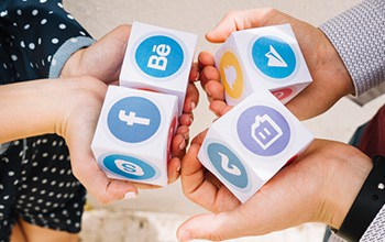 elevated-view-of-human-hands-holding-blocks-of-mobile-application-icons_23-2147844581
